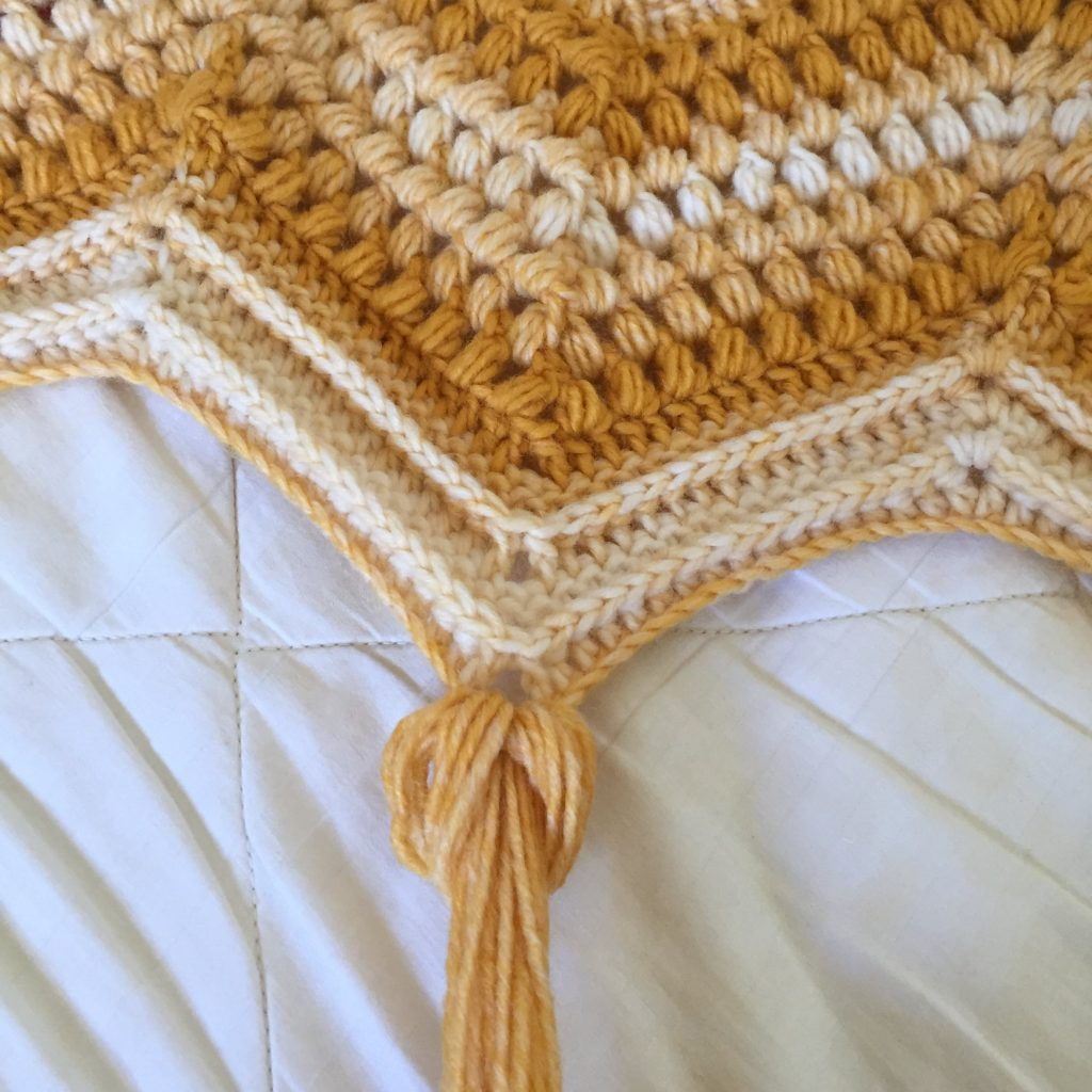 Attaching a Yellow Tassel to a Crochet Blanket