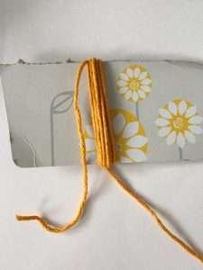 Wrap yarn around cardboard to make a tassel