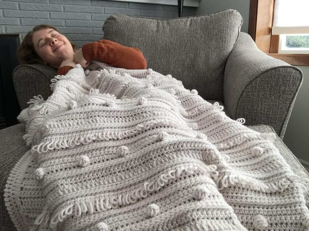 Cuddling under the Loops and Bobbles Crochet Blanket
